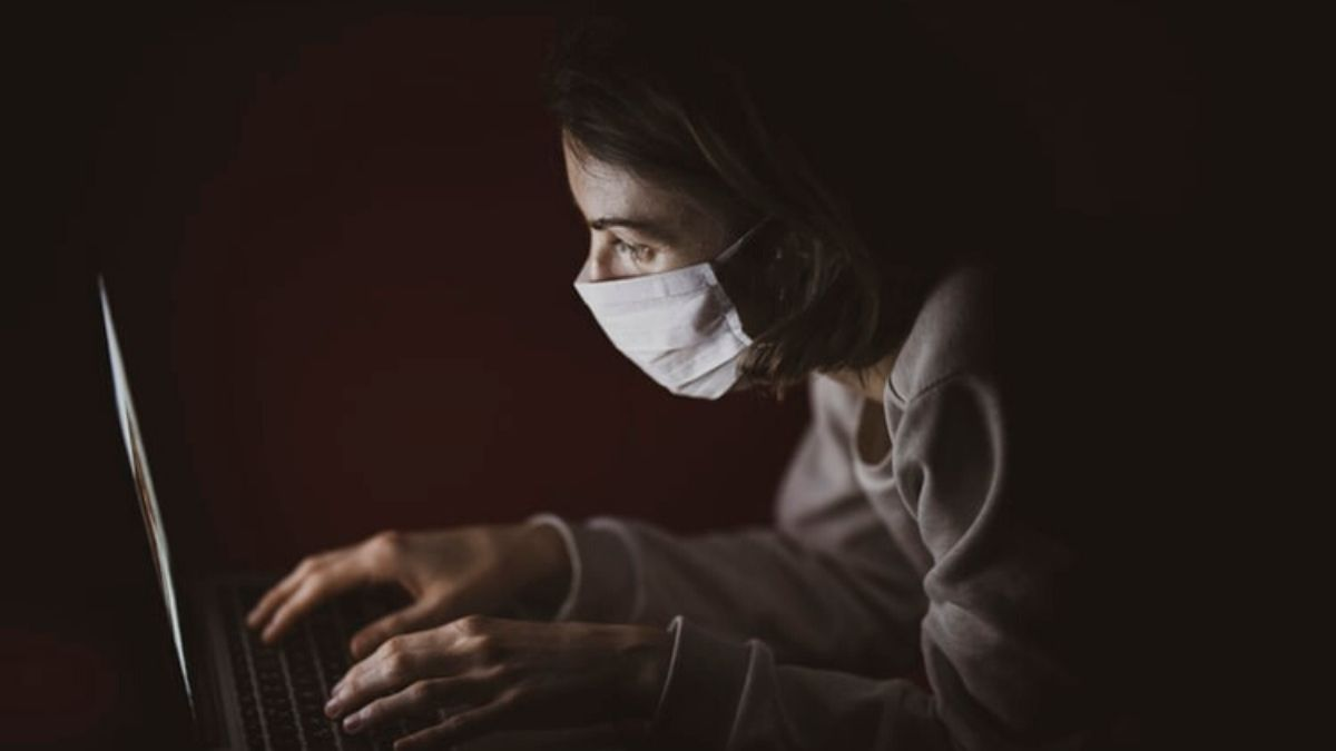 Woman Wearing Mask Using Laptop