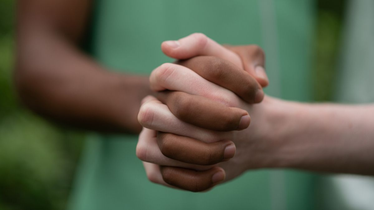Men With Different Skin Color Holding Hands Together