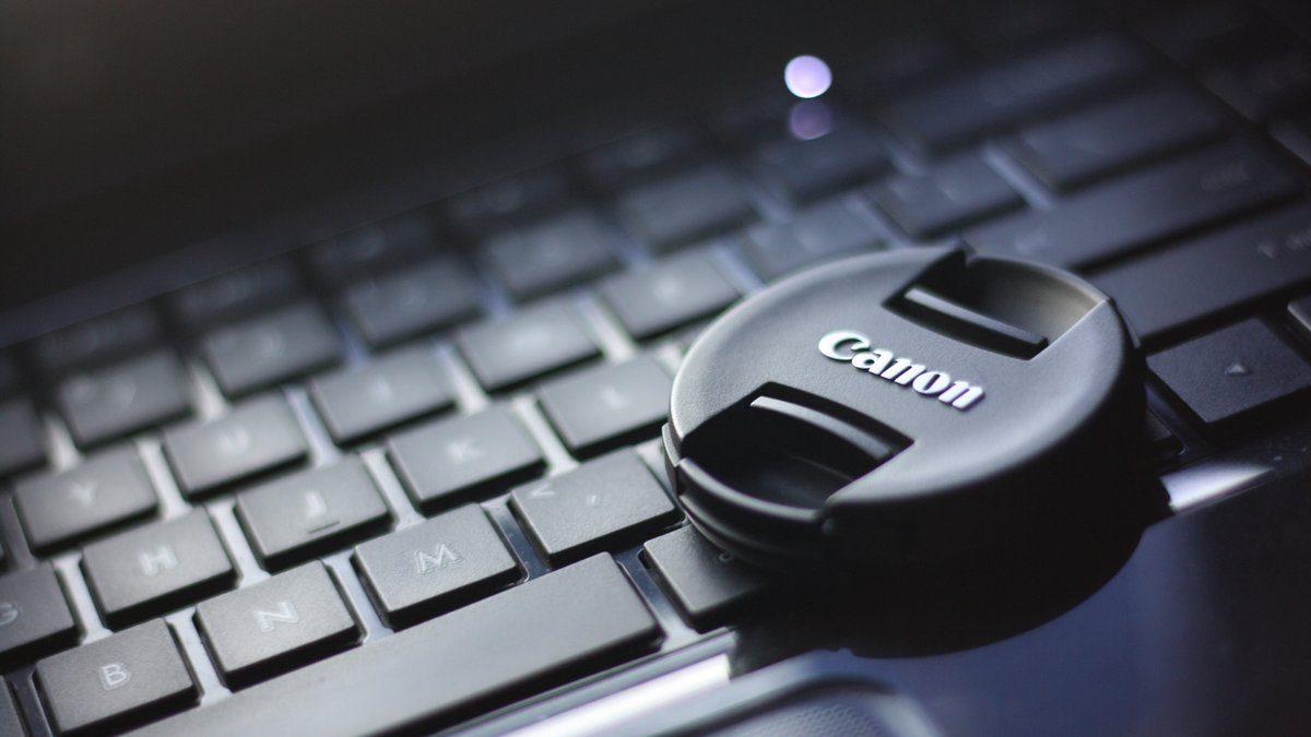 Black Canon Camera Above Laptop