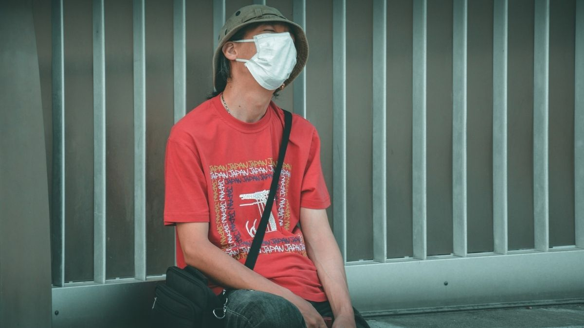 A Man Wearing Protective Mask Sitting On Bench