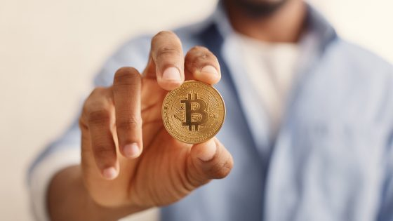 A Man Holds Bitcoin In Hand