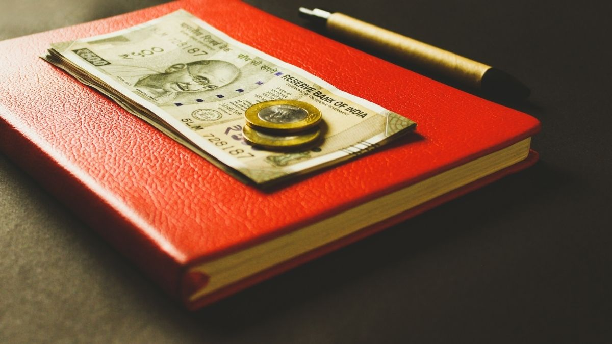 Indian Rupees Placed On A Book And A Pen