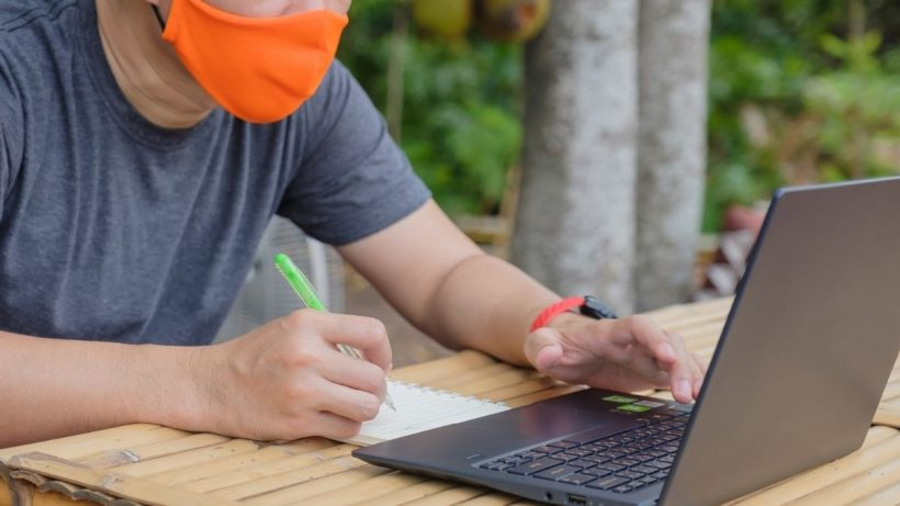 A Person Wearing Mask Working Online