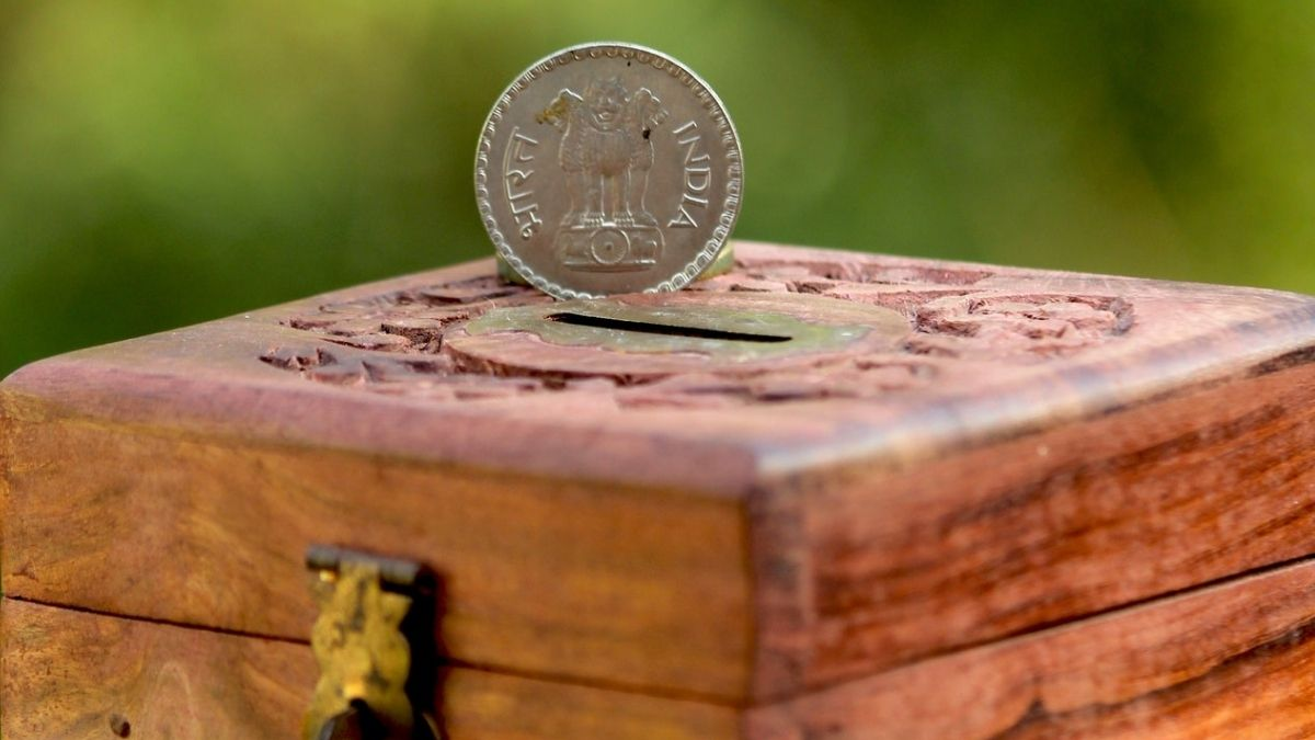 A Coin Placed Above A Box