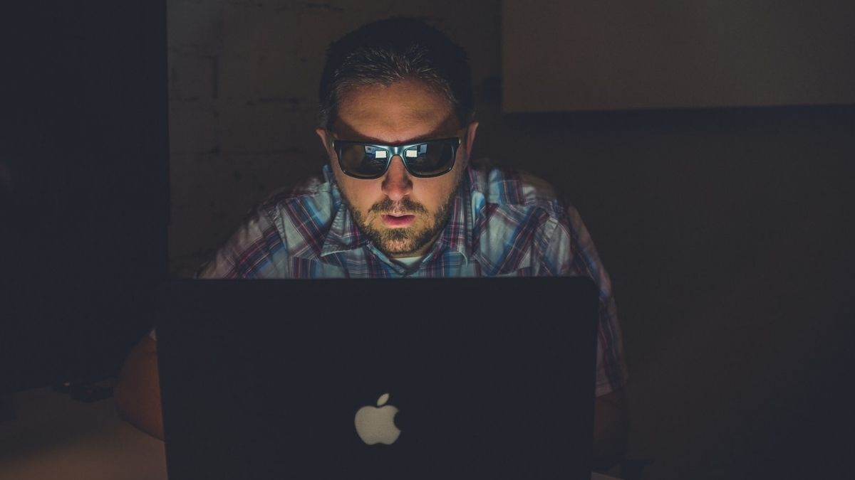 Man With Black Goggles Using Macbook