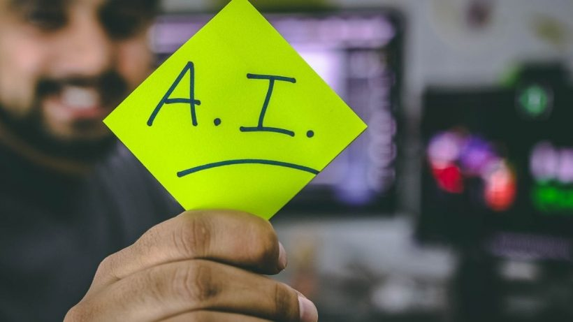 Man Holding Paper With AI Written On It