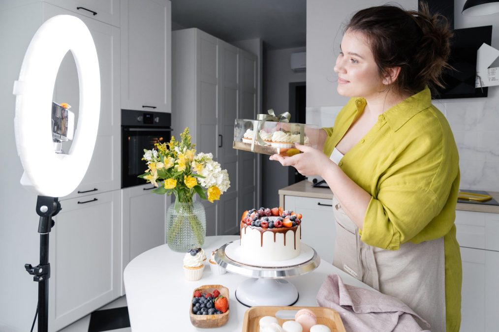 smiling vlogger showing delicious cakes while filming video